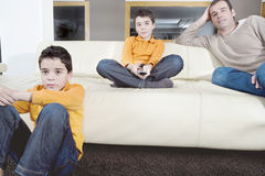 Dad and children watching tv. Father and identical twin sons watching tv in the living room at home Stock Image