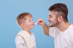 A dad cleans his small son`s teeth. Blue background. royalty free stock photo