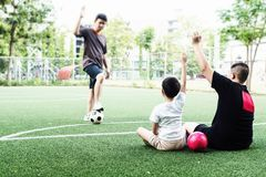 Dad coaches his children how to play soccer. Or football in green football field - outdoor family sport activity concept royalty free stock image