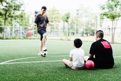 Dad coaches his children how to play soccer. Or football in green football field - outdoor family sport activity concept stock image