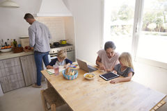 Dad cooking and mum with kids at kitchen table, high angle Royalty Free Stock Photo