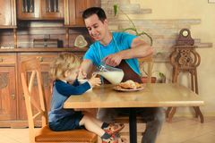 Dad cooks a breakfast. Man with little boy in the kitchen preparing a meal. retro Royalty Free Stock Photos