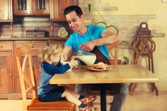 Dad cooks a breakfast. Man with little boy in the kitchen preparing a meal. retro Royalty Free Stock Photography
