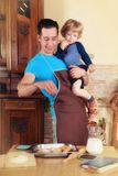 Dad cooks. Man with little boy in the kitchen preparing a meal. retro Royalty Free Stock Photos