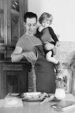 Dad cooks. Man with little boy in the kitchen preparing a meal. retro Royalty Free Stock Images