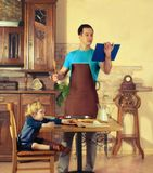 Dad cooks. Man with little boy in the kitchen preparing a meal. retro Stock Photography
