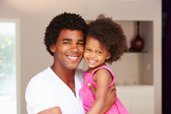 Dad Cuddling Daughter At Home Stock Photo