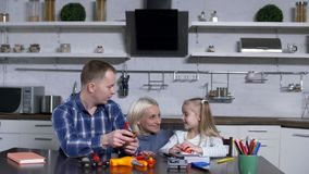 Dad with cute girl at shop class in domestic kitchen. Father teaching tooling elementary school daughter, showing on toy tool kit tightening screw on bolt while stock video