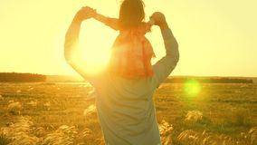 Dad dancing on his shoulders with his daughter in sun. Father travels with baby on his shoulders in rays of sunset. A. Dad dancing on his shoulders with his stock photography