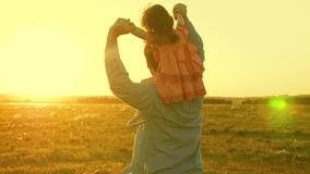Dad dancing on his shoulders with his daughter in sun. Father travels with baby on his shoulders in rays of sunset. A. Dad dancing on his shoulders with his royalty free stock photo