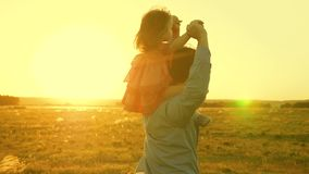 Dad dancing on his shoulders with his daughter in sun. Father travels with baby on his shoulders in rays of sunset. A. Dad dancing on his shoulders with his royalty free stock photos