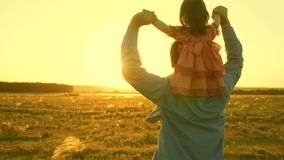 Dad dancing on his shoulders with his daughter in sun. Father travels with baby on his shoulders in rays of sunset. A. Dad dancing on his shoulders with his stock image