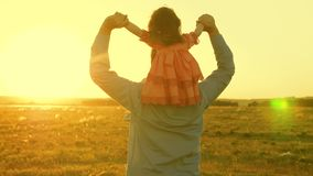 Dad dancing on his shoulders with his daughter in sun. Father travels with baby on his shoulders in rays of sunset. A. Dad dancing on his shoulders with his royalty free stock photography