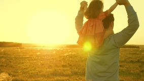 Dad dancing on his shoulders with his daughter in sun. Father travels with baby on his shoulders in rays of sunset. A. Dad dancing on his shoulders with his royalty free stock image