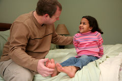 Dad and Daughter. Dad tickles his daughter before she goes to bed stock photography