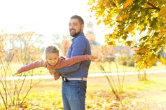 Dad and daughter in the autumn park play laughing.  royalty free stock photography