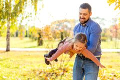 Dad and daughter in the autumn park play laughing.  stock photo
