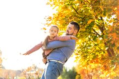 Dad and daughter in the autumn park play laughing.  stock photography