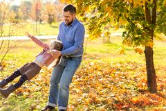 Dad and daughter in the autumn park play laughing stock image