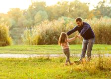 Dad and daughter in the autumn park play laughing. Park at sunset of the day royalty free stock photography