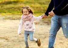 Dad and daughter in the autumn park play laughing. Park at sunset of the day stock photography