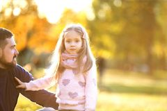 Dad and daughter in the autumn park play laughing. An evening walk in the park royalty free stock images