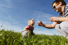 Dad and daughter blow bubbles Stock Photo