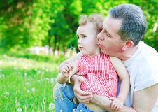 Dad and daughter blow out the dandelions Royalty Free Stock Image