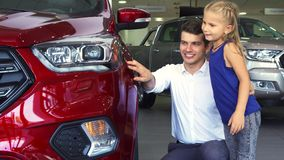 A young father and daughter are standing near one of the cars stock image
