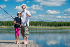 Dad and daughter caught a fish on a river. Dad with his daughter on the pier caught fish in the river Stock Images