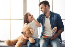 Dad and daughter. Charming little girl and her handsome young dad are reading a book and smiling while sitting on the window sill at home stock photo