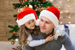 Dad and daughter, Christmas hat, tree, gift box stock image