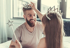 Dad and daughter. Cute little girl and her handsome bearded dad in crowns are smiling while playing in her room stock photo