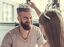 Dad and daughter. Cute little girl and her handsome bearded dad in crowns are smiling while playing in her room royalty free stock images