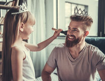 Dad and daughter. Cute little girl and her handsome bearded dad in crowns are smiling while playing in her room. Girl is doing her dad makeup royalty free stock photos