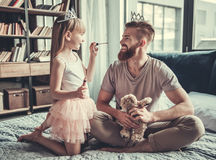 Dad and daughter. Cute little girl and her handsome bearded dad in crowns are smiling while playing in her room. Girl is doing her dad makeup stock photo