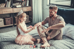 Dad and daughter. Cute little girl and her handsome bearded dad in crowns are smiling while playing in her room. Girl is painting her dad nails royalty free stock image