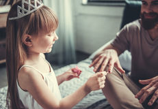 Dad and daughter. Cute little girl and her handsome bearded dad are playing in her room. Girl is painting her dad nails stock images