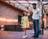 Dad with daughter. Dad is dancing with his daughter on house`s terrace royalty free stock photo