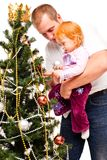 Dad with daughter decorate a new-year tree Stock Photo