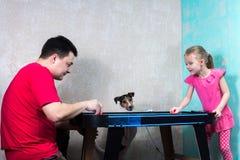 Dad daughter and dog playing air hockey. Dad daughter and dog are playing air hockey Stock Photo