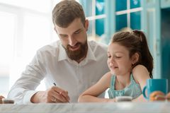 Dad and daughter doing homework. Together. Family`s support, friendly atmosphere and school education royalty free stock photo