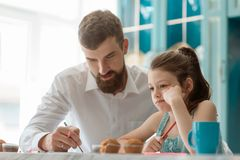 Dad and daughter doing homework. Dad and tired daughter doing homework together. Father`s care and support for his overworked child royalty free stock photography