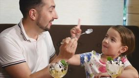 Dad and daughter eating ice cream in cafe stock video
