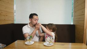 Dad and daughter eating ice cream in cafe stock footage