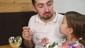 Dad and daughter eating ice cream in cafe stock video footage