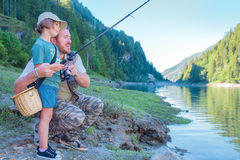 Dad and daughter are fishing together in a lake in the mountains Royalty Free Stock Image