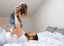 Dad and daughter have fun at home on the bed. Father`s Day royalty free stock photography