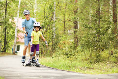 Dad and daughter in a helmet. Portrait of a sports dad and daughter in a helmet. Dad with his little daughter on the skates. two people rollerblade Stock Photos