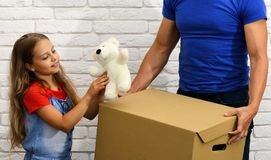 Dad and daughter hold cardboard box. Moving in or out. Concept. Girl plays with white teddy bear on white brick wall background. Deliveryman or father and child Stock Photos
